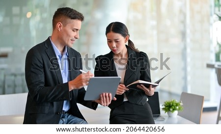 Helpful male boss mentor coach explaining marketing strategy campaign to young asian female worker via digital tablet computer in the office.