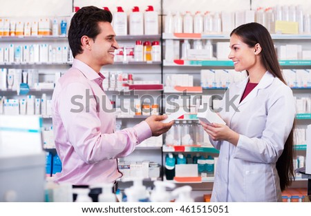 Helpful pharmacist serving and consulting man in a pharmacy