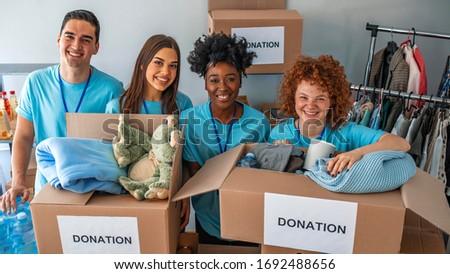 Helpful team of social workers. Group of mixed race people working in charitable foundation. Small group of people working on humanitarian aid project. We will meke someone smile again Stock fotó ©