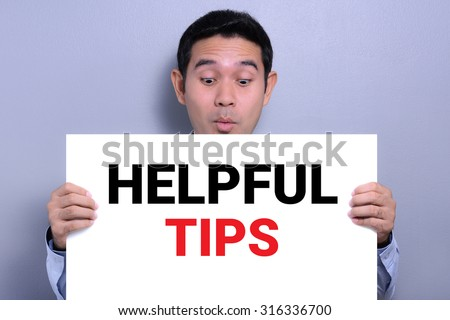 HELPFUL TIPS message on white cardboard held by a man with excited face