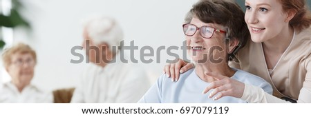 Helpful volunteer taking care of senior lady at healthcare home