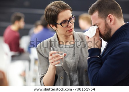 Helpful woman offering glass of water to crying man
