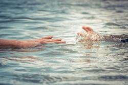 Helping adult hand reaching child hand drowning in water concept water rescue safety