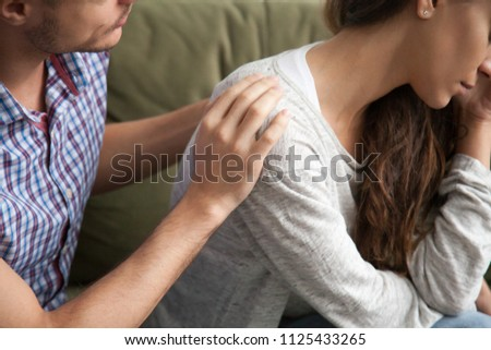 Helping caring husband apologizing comforting wife, understanding man expressing sympathy encouraging upset woman, apology and forgiveness, support in marriage concept, hand on shoulder close up view