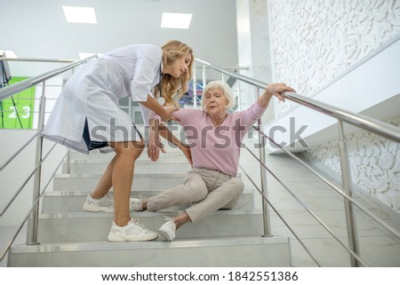Helping hand. Blonde nurse helping the senior woman who fell down on the strairs Stock photo ©