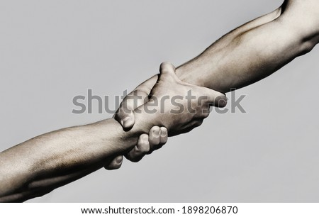 Helping hand concept and international day of peace, support. Helping hand outstretched, isolated arm, salvation. Close up help hand. Two hands, helping arm of a friend, teamwork. Black and white. Stock photo ©