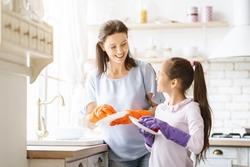 Helping hand. Cute Teenage Girl Help Her Mother In Washing Dishes At Family Kitchen
