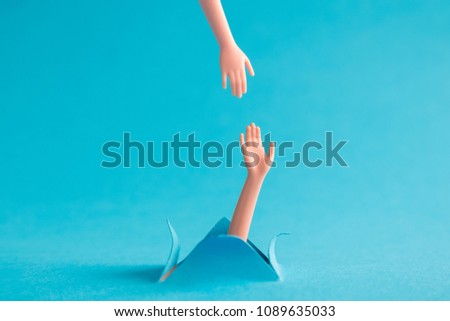 Helping hand to drowning person minimal creative concept.