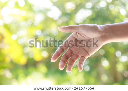 Helping hands  against bright nature background