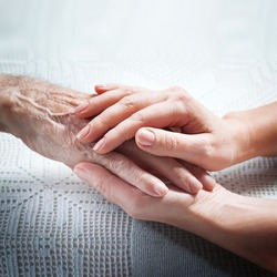 Helping hands, care for the elderly concept. Care is at home of elderly.