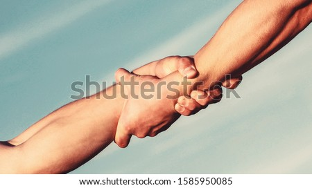 Helping hands concept, support. Close up help arm and international day of peace, support. Hands of on blue sky background.