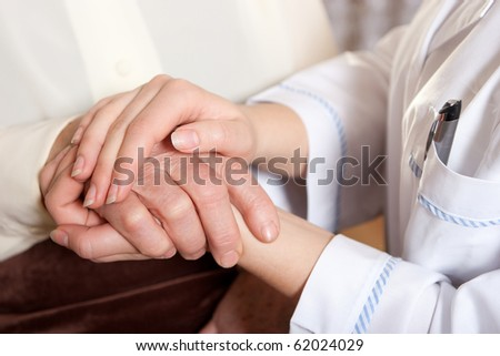 Helping hands: the nurse holds hands of the elderly female - stock photo