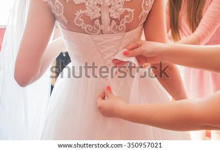 Shutterstock Helping the bride to put her wedding dress on