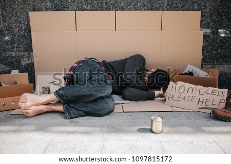 Helpless and defenceless man is lying on the cardboard on concrete floor and sleeping. He is covering his face with hands hiding it from the sun. There is a sign besides him says homeless please help.