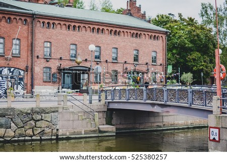 HELSINKI, FINLAND - CIRCA SEPTEMBER 2016: red brick buildings by the river in popular among youth Kallio district of Helsinki, Finland circa September 2016. #525380257