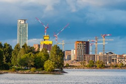 Helsinki. Finland. Construction of houses on the Baltic sea. Erection of buildings. Housing construction in Helsinki. Accommodation on the Gulf of Finland. Hoisting cranes against the gray sky.