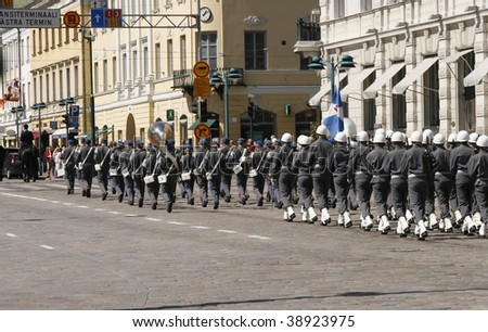 HELSINKI, FINLAND - JUNE 1: A small military parade interrupted business at the market as vendors and buyers alike ran to the street to watch the parade on June 1, 2007 in Helsinki, Finland - stock photo