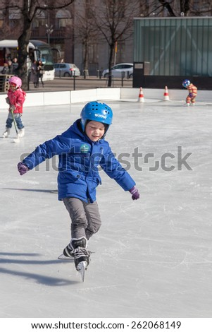 HELSINKI ,FINLAND-MARCH 29 2014:Children skate on an outdoor ice rink,HELSINKI ,FINLAND-MARCH 29 2014. In the cities of Finland it is opened in the winter works hard outdoor ice rinks.