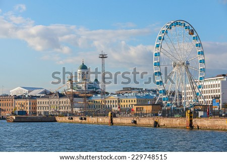 Helsinki, Finland - September 13, 2014: central quay of Helsinki with moored ships, central Cathedral and ferris wheel