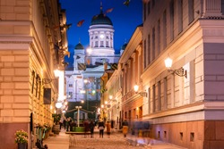 Helsinki. Finland. Suurkirkko. Cathedral Of St. Nicholas. Cathedrals Of Finland. The street leads to Helsinki Senate square. Helsinki travel guide. Architecture. White Church with dark domes.