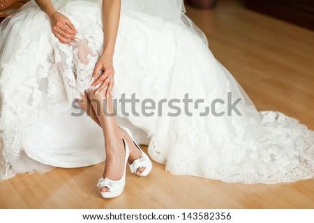 Shutterstock Hem of her dress. Bride shoes. Lace train wedding dress.