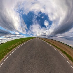 hemisphere of the planet on an asphalt road stretching beyond the horizon with blue sky and beautiful clouds. Spherical abstract aerial view. Curvature of space.