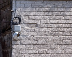 hemispherical shape, surveillance camera connected to the network and mounted on the wall of a brick house