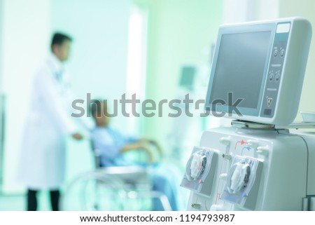 Hemodialysis machines with tubing and installations. Asian patient in wheelchair sitting in hospital corridor with Asian male doctor, medical equipment concept.