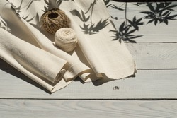 Hemp canvas and threads on a white wooden surface