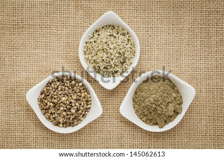 hemp products: seeds, hearts (shelled seeds) and protein powder in small ceramic bowls on burlap canvas
