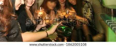 hen-party. woman pours champagne into glasses for girlfriends. female sit at the car and drink champagne together. bachelorette party. no faces. Foto stock ©