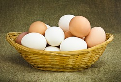 Hen's Eggs in a Woven Straw Basket on a Sacking background