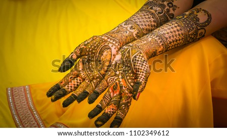 Henna painting, mehendi on bride's hands with the yellow dress background. Wedding preparation in India. Stock photo ©