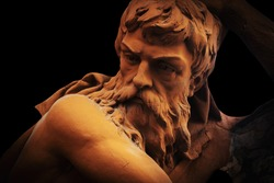 Hephaestus. In Greek and Roman mythology god of the forge and blacksmiths. Close up an ancient statue. Horizontal image.