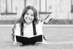 Her hobby is literature. Happy small child read childrens literature outdoor. Adorable little girl enjoy reading English literature at leisure. Learning foreign literature at school.
