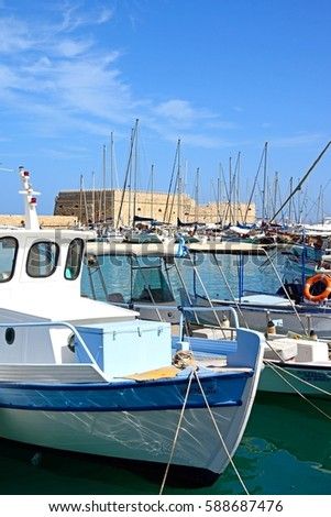 HERAKLION, CRETE - SEPTEMBER 19, 2016 - Traditional fishing boats moored in the harbour with Koules castle to the rear, Heraklion, Crete, Greece, Europe, September 19, 2016. #588687476