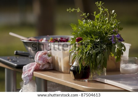 Herb Bouquet and a bottle of balsamic vinegar on a table in outdoor kitchen - stock photo