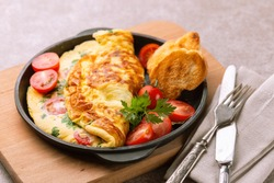 Herb omelette with chives, cherry tomatoes and parsley with panini toasts. Breakfast