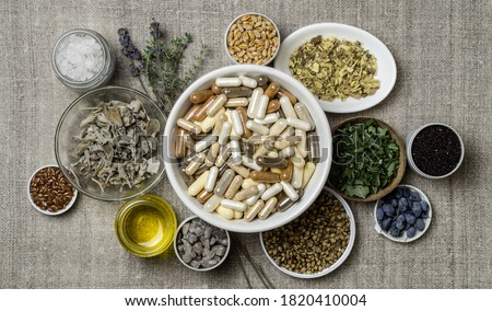 Herbal and mineral organic dietary supplements in capsules. Ingredients in for food supplements in plates