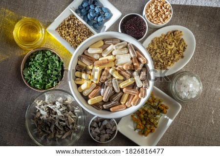 Herbal and mineral organic dietary supplements in capsules. Ingredients in for food supplements in plates Stock photo ©
