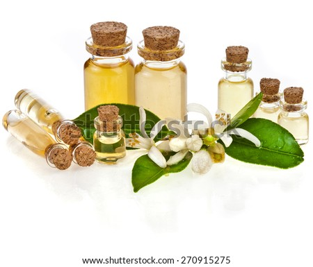 Herbal aromatherapy essential oil in bottles with fresh citrus flowers isolated on white