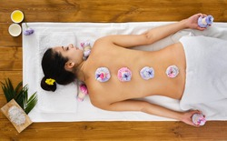 Herbal ball massage in ayurveda spa.Young woman in wellness center. Healthcare therapy to beautiful indian girl in beauty parlor, top view from the back, laying on wood