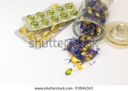 herbal capsules and dried herbs cornflower on white