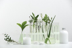 Herbal cosmetic products, laboratory glassware and ingredients on white table