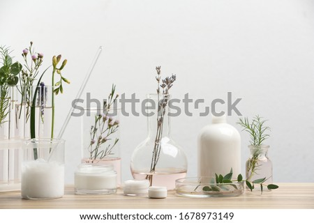 Herbal cosmetic products, laboratory glassware and ingredients on wooden table