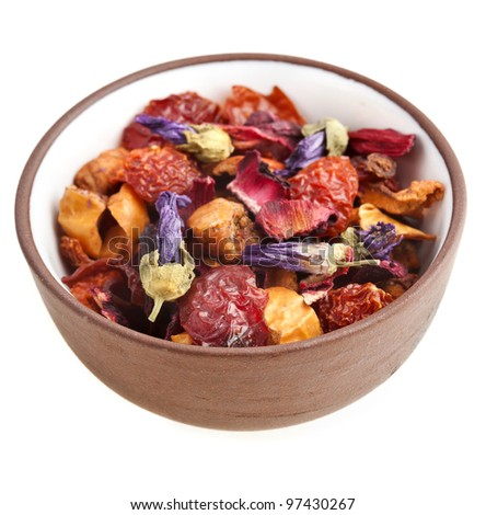 herbal fruit tea with petals and dry berries on clay cup , isolated on white background