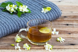 herbal healthy drinks hot lemon tea health care for cough sore with lemon slice ,jasmine flowers and knitting wool scarf of lifestyle woman relax winter arrangement flat lay style on background wooden