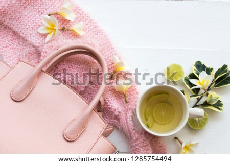 herbal honey lemon healthy drinks health care for sore throat with pink  knitting wool scarf ,pink bag of lifestyle woman relax in winter season and flowers frangipani decorate on background white