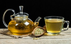 Herbal infusion fennel tea in glass cup and glass tea pot with dried fennel seeds in wooden shovel. Herbal tea alternative medicine background concept.