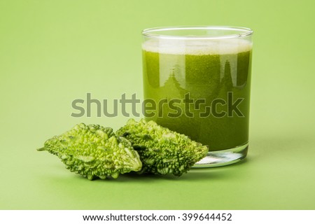 Shutterstock Herbal juice of green momodica in a glass with sliced vegetables, karela juice or bitter gourd juice
